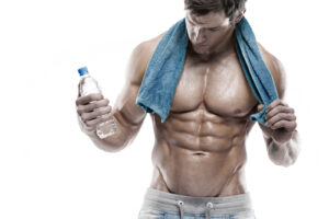 Strong Athletic Man Fitness Model Torso showing six pack abs. holding bottle of water and towel